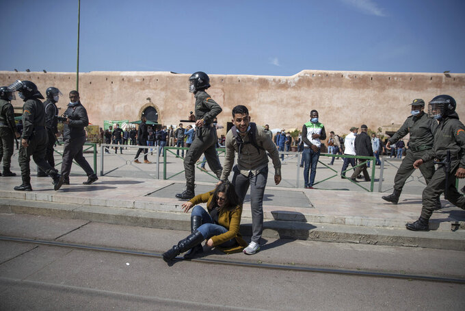 A protester helps a woman as security forces disperse a demonstration staged by teachers demanding improved job conditions, in Rabat, Morocco, Tuesday, March 16, 2021. (AP Photo/Mosa'ab Elshamy)