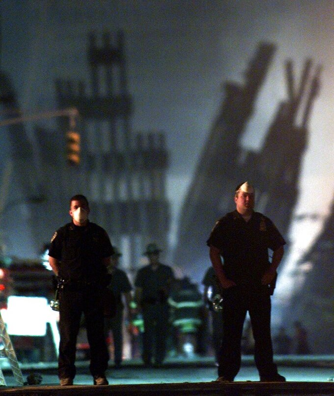 FILE - In this Sept. 12, 2001, file photo, policemen stand guard near the site of the World Trade Center in New York.  (AP Photo/Beth A. Keiser)