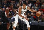 Milwaukee Bucks forward Giannis Antetokounmpo, right, looks to pass as Portland Trail Blazers forward Al-Farouq Aminu, left, defends during the first half of an NBA basketball game in Portland, Ore., Tuesday, Nov. 6, 2018. (AP Photo/Steve Dipaola)