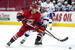 Carolina Hurricanes defenseman Jake Bean (24) and Tampa Bay Lightning center Blake Coleman (20) chase the puck during the first period of an NHL hockey game in Raleigh, N.C., Monday, Feb. 22, 2021. (AP Photo/Gerry Broome)