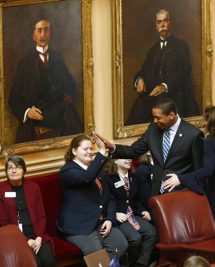 Virginia Lt. Gov. Justin Fairfax, right, gives a high five to a page as he prepares for the start of the Senate session at the Capitol in Richmond, Va., Friday, Feb. 8, 2019. (AP Photo/Steve Helber)
