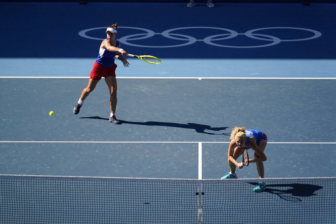 Barbora Krejcikova, of the Czech Republic, returns a shot during the women's doubles gold medal match of the tennis competition against Switzerland at the 2020 Summer Olympics, Sunday, Aug. 1, 2021, in Tokyo, Japan. (AP Photo/Seth Wenig)