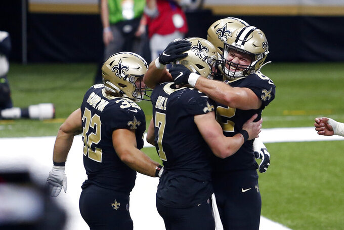 New Orleans Saints quarterback Taysom Hill (7) celebrates his touchdown carry with tight end Adam Trautman (82) and running back Michael Burton (32) in the second half of an NFL football game against the Atlanta Falcons in New Orleans, Sunday, Nov. 22, 2020. (AP Photo/Brett Duke)