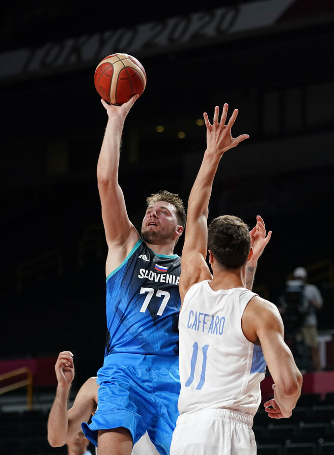 Slovenia's Luka Doncic (77) drives to the basket over Argentina's Francisco Caffaro (11) during men's basketball preliminary round game at the 2020 Summer Olympics, Monday, July 26, 2021, in Saitama, Japan. (AP Photo/Charlie Neibergall)