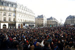 A crowd listens to musicians performing outside the Palais Garnier opera house, Saturday, Jan. 18, 2020 in Paris. As some strikers return to work, with notable improvements for train services that have been severely disrupted for weeks, more radical protesters are trying to keep the movement going. (AP Photo/Thibault Camus)