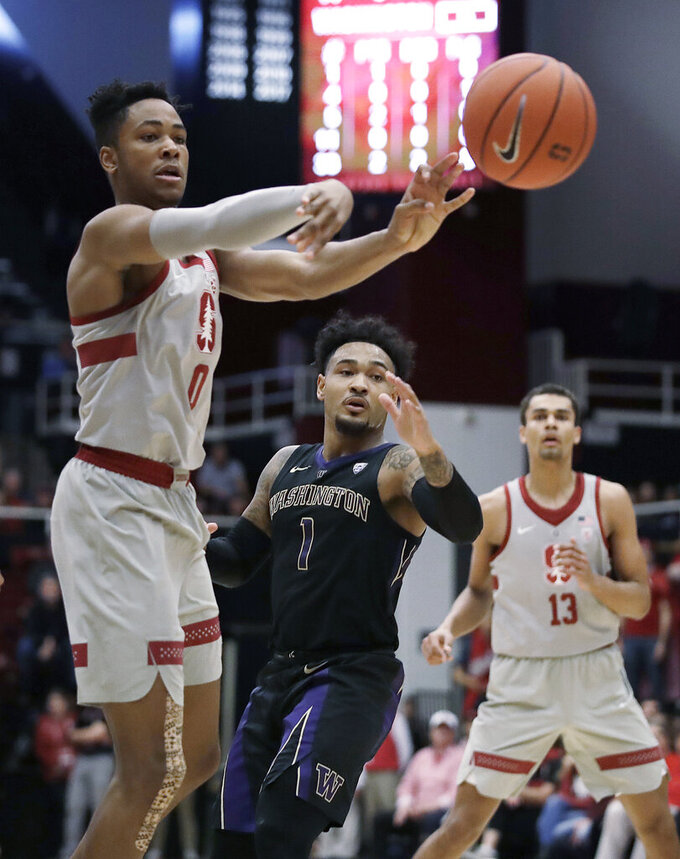 Stanford's KZ Okpala, left, passes away from Washington's David Crisp (1) in the first half of an NCAA college basketball game Sunday, March 3, 2019, in Stanford, Calif. (AP Photo/Ben Margot)