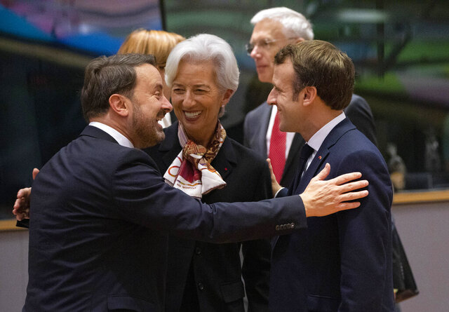 European Central Bank President Christine Lagarde, center, speaks with Luxembourg's Prime Minister Xavier Bettel, left, and French President Emmanuel Macron, right, during a round table meeting at an EU summit in Brussels, Friday, Dec. 13, 2019. European Union leaders are gathering Friday to discuss Britain's departure from the bloc amid some relief that Prime Minister Boris Johnson has secured an election majority that should allow him to push the Brexit deal through parliament. (AP Photo/Olivier Matthys)