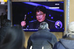 People watch a TV screen showing an image of South Korean director Bong Joon Ho during a news program at the Seoul Railway Station in Seoul, South Korea, Monday, Feb. 10, 2020. In a milestone win that instantly expanded the Oscars' horizons, Bong's masterfully devious class satire