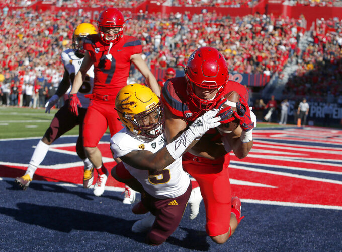 Arizona wide receiver Shawn Poindexter, right, catches a touchdown pass while being defended by Arizona safety Christian Young (5) in the first half during an NCAA college football game, Saturday, Nov. 24, 2018, in Tucson, Ariz. (AP Photo/Rick Scuteri)