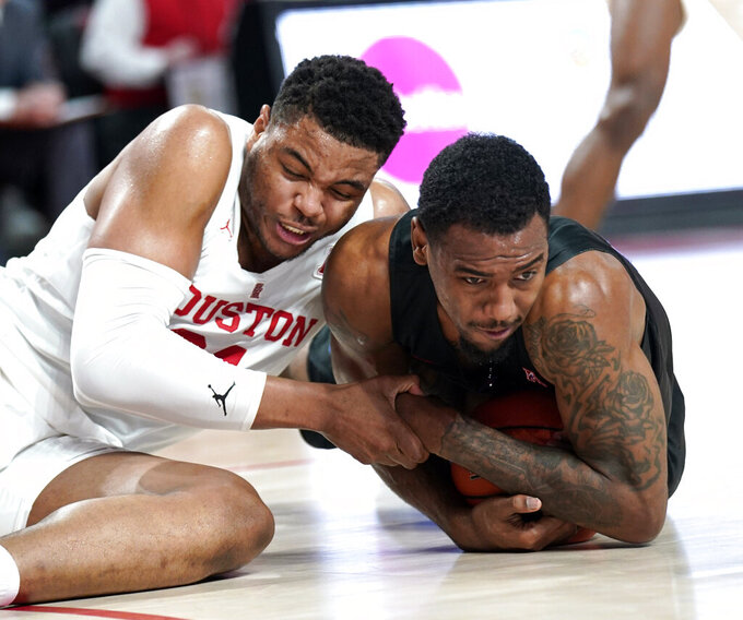 Houston's Breaon Brady, left, and Southern Methodist's Isiaha Mike reach for a loose ball during the first half of an NCAA college basketball game Thursday, March 7, 2019, in Houston. (AP Photo/David J. Phillip)
