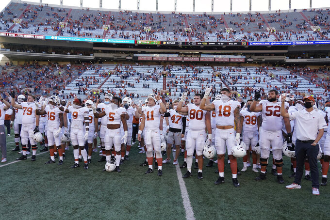 "FILE - In this Saturday, Oct. 24, 2020, file photo, Texas players, including Sam Ehlinger (11), sing ""The Eyes Of Texas"" after an NCAA college football game against Baylor in Austin, Texas. The University of Texas marching band and pep band will be required to play ""The Eyes of Texas"" school song when they return to performing, but the school will also create a new band that doesn't include it in its play list, the school has announced. The song has been mired in controversy since summer 2020 when a group of athletes and students called on the school to ditch the tune amid national racial injustice protests after the killing of George Floyd. (AP Photo/Chuck Burton, File)"