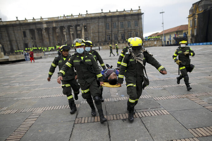 Police carry an anti-government protesters affected by tear gas after clashes at the Bolivar square in downtown Bogota, Colombia, Friday, Nov. 22, 2019. Labor unions and student leaders called on Colombians to bang pots and pans Friday evening in another act of protest while authorities announced three people had died in overnight clashes with police after demonstrations during a nationwide strike. (AP Photo/Ivan Valencia)