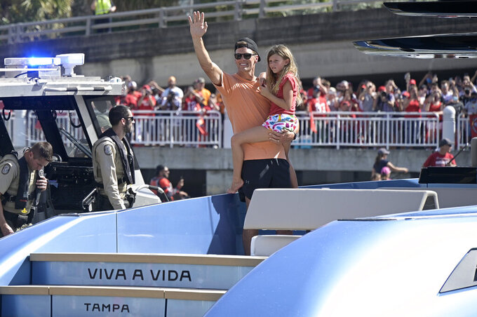 Tampa Bay Buccaneers quarterback Tom Brady holds his daughter Vivian Lake while waving to fans during a celebration of their Super Bowl 55 victory over the Kansas City Chiefs with a boat parade, Wednesday, Feb. 10, 2021, in Tampa, Fla. (AP Photo/Phelan M. Ebenhack)