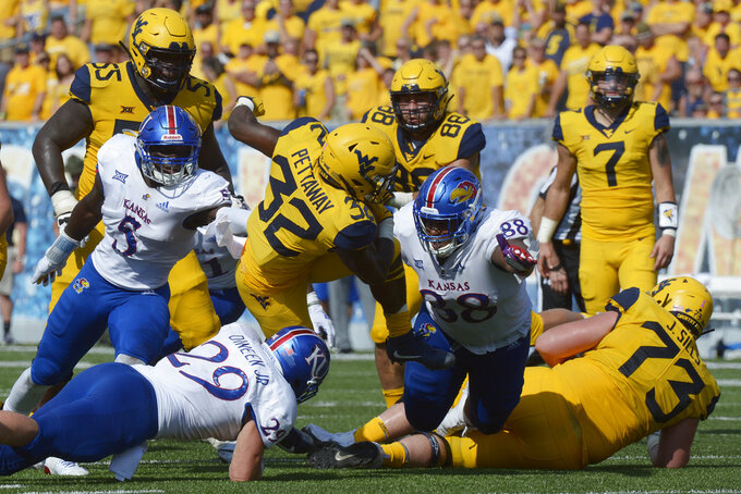 West Virginia running back Martell Pettaway (32) is brought down by Kansas linebacker Joe Dineen Jr. (29) during the second half of an NCAA college football game  in Morgantown, W. Va., Saturday Oct. 6, 2018. (AP Photo/Craig Hudson)