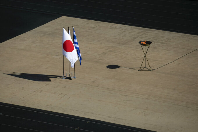 The Japanese flag flies next to an altar with the Olympic Flame of the Tokyo 2020 Olympic Games, inside the Panathenian stadium, in Athens, Sunday, March 15, 2020. The Panathenian Stadium will be closed to the spectators on Thursday, March 19 during the handover ceremony of the Olympic flame for the Tokyo 2020 Olympic Games as a precaution against the spread of the coronavirus. The vast majority of people recover from the new coronavirus. According to the World Health Organization, most people recover in about two to six weeks, depending on the severity of the illness. (AP Photo/Yorgos Karahalis)