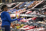 A customer shops at the meat counter at a Walmart Neighborhood Market, Wednesday, April 24, 2019, in Levittown, N.Y. Walmart can rely on thousands of cameras hanging from the ceiling that track when products are running low or when produce or meat start to lose their freshness. (AP Photo/Mark Lennihan)