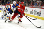 Detroit Red Wings left wing Andreas Athanasiou moves the puck away from St. Louis Blues center Tyler Bozak in the second period of an NHL hockey game, Sunday, Oct. 27, 2019. (AP Photo/Jose Juarez)