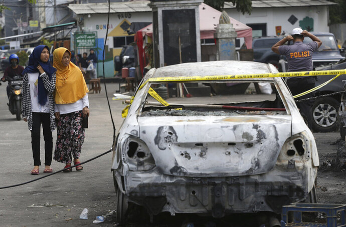 Muslim women walk near a burnt car in Jakarta, Indonesia, Wednesday, May 22, 2019. Supporters of the losing presidential candidate burned vehicles and battled police and the government announced restrictions on social media. (AP Photo/Achmad Ibrahim)