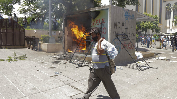 A Chivo digital wallet ATM, which exchanges cash for Bitcoin cryptocurrency, burns after being torched during a protest against President Nayib Bukele in San Salvador, El Salvador, Wednesday, Sept. 15, 2021. Thousands marched against the government of President Bukele, centered on fears Bukele may try for re-election in 2024. (AP Photo/Ivan Manzano)
