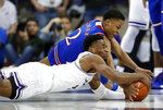 TCU guard RJ Nembhard, front, and Kansas guard Charlie Moore (2) wrestle on the floor for control of a loose ball in the first half of an NCAA college basketball game in Fort Worth, Texas, Monday, Feb. 11, 2019. (AP Photo/Tony Gutierrez)