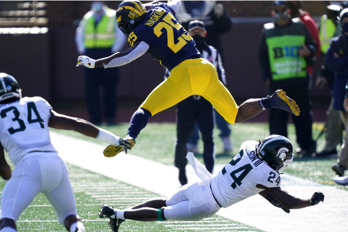 Michigan running back Hassan Haskins (25) jumps over Michigan State safety Tre Person (24) during the first half of an NCAA college football game, Saturday, Oct. 31, 2020, in Ann Arbor, Mich. (AP Photo/Carlos Osorio)