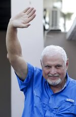 Former Panamanian President Ricardo Martinelli waves to journalist at his home, after his release from jail in Panama City, Wednesday, June 12, 2019. A Panamanian court ordered that former President Martinelli to be transferred from jail to house arrest. (AP Photo/Arnulfo Franco)
