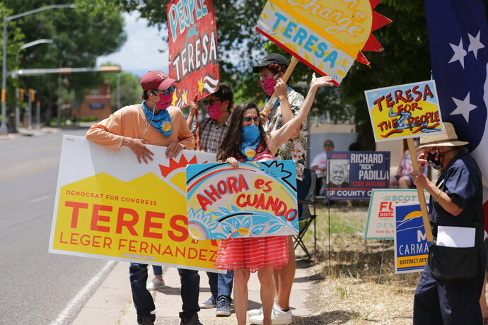 Democratic congressional candidate Teresa Leger Fernandez, in the blue mask, cheers on supporters at a polling station on Tuesday, June 2, 2020, in Santa Fe, N.M. Behind her are her three sons, from left, Dario, Abelino and Alisandro. The sign she holds,