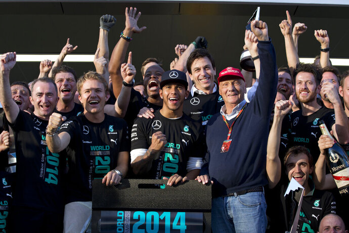 FILE - In this Sunday, Oct. 12, 2014 file photo Mercedes team drivers Lewis Hamilton of Britain, right, winner of the race, flanked by his teammate second place Nico Rosberg of Germany and Mercedes non-Executive Chairman former F1 driver Niki Lauda celebrate with all team members after the Formula One Russian Grand Prix at the 'Sochi Autodrom' Formula One circuit, in Sochi, Russia. Three-time Formula One world champion Niki Lauda, who won two of his titles after a horrific crash that left him with serious burns and went on to become a prominent figure in the aviation industry, has died. He was 70. (AP Photo/Pavel Golovkin, File)