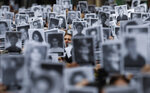 A man stands amid pictures of victims of the bombing of the AMIA Jewish center that killed 85 people, on the 25th anniversary of the attack in Buenos Aires, Argentina, Thursday, July 18, 2019. (AP Photo/Natacha Pisarenko)