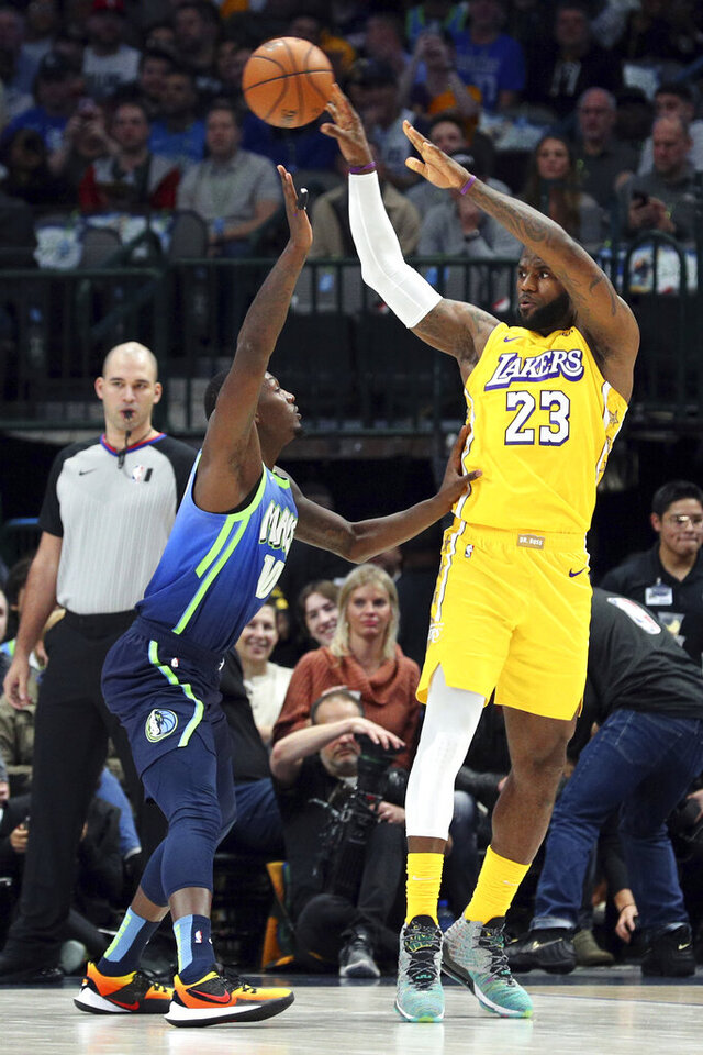 Los Angeles Lakers forward LeBron James (23) passes the ball over Dallas Mavericks forward Dorian Finney-Smith (10) during the first half of an NBA basketball game Friday, Jan. 10, 2020, in Dallas. (AP Photo/Richard W. Rodriguez)
