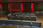 A man sits alone on a bench monitors stock prices at a brokerage house in Beijing, Tuesday, May 14, 2019. Shares opened moderately lower in Asia on Tuesday after a dismal day on Wall Street as investors fled uncertainty over the China-U.S. trade standoff. (AP Photo/Andy Wong)