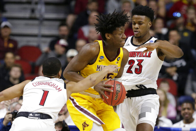 Minnesota's Daniel Oturu (25) tries to get past Louisville's Steven Enoch (23) with Christen Cunningham (1) defending, during the first half of a first round men's college basketball game in the NCAA Tournament, in Des Moines, Iowa, Thursday, March 21, 2019. (AP Photo/Nati Harnik)