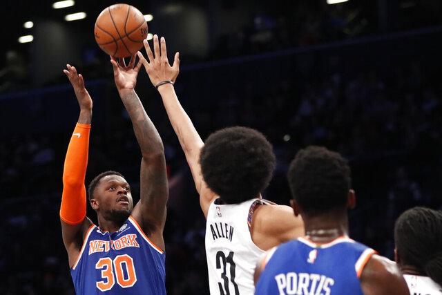New York Knicks forward Julius Randle (30) shoots with Brooklyn Nets center Jarrett Allen (31) defending and Knicks forward Bobby Portis (1) watching during the first half of an NBA basketball game, Thursday, Dec. 26, 2019, in New York. (AP Photo/Kathy Willens)