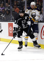 Los Angeles Kings' Drew Doughty, left, presses Buffalo Sabres' Zemgus Girgensons against the boards during the first period of an NHL hockey game Thursday, Oct. 17, 2019, in Los Angeles. (AP Photo/Marcio Jose Sanchez)