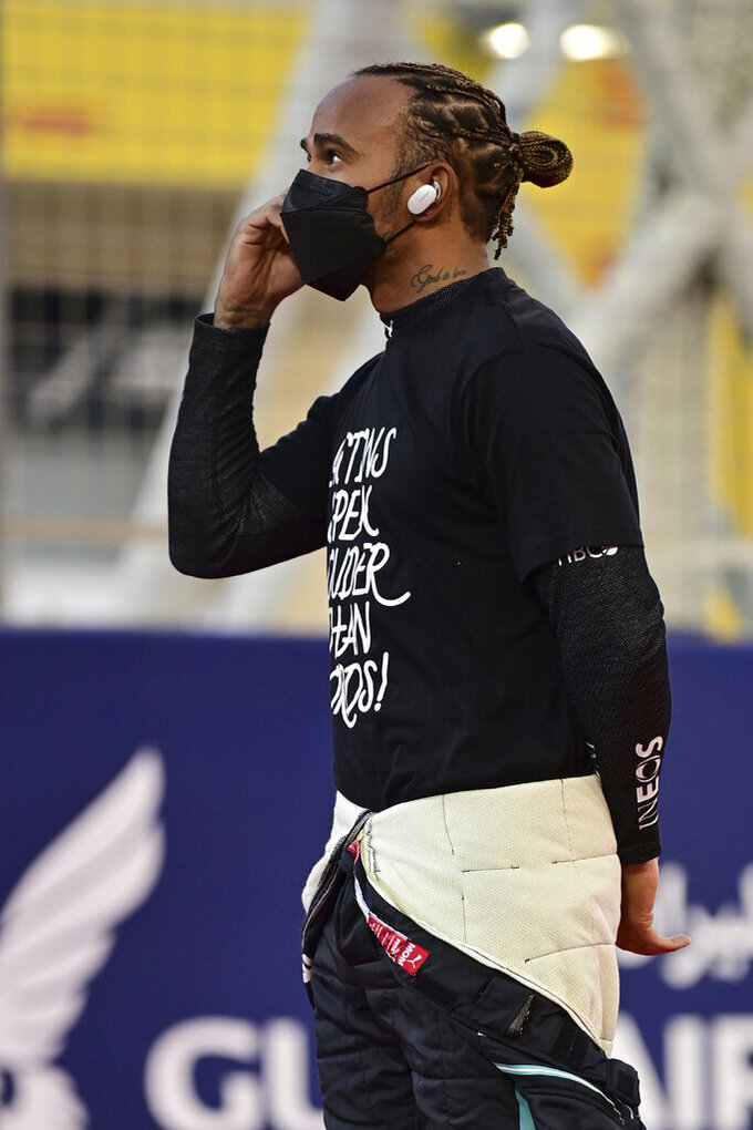 Mercedes driver Lewis Hamilton of Britain speaks on his mobile phone at the starting grid prior to the start of the Bahrain Formula One Grand Prix at the Bahrain International Circuit in Sakhir, Bahrain, Sunday, March 28, 2021. (Andrej Isakovic, Pool via AP)