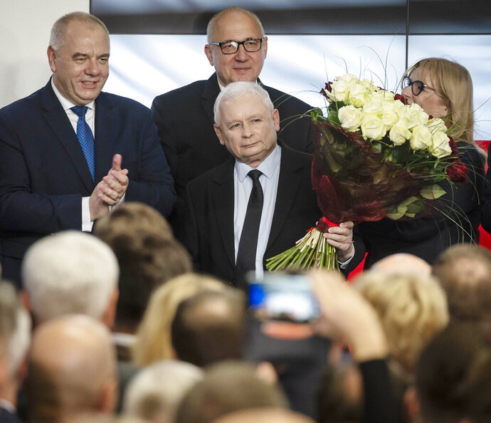 Leader of Poland's ruling party Jaroslaw Kaczynski, center, and party activists react to exit poll results right after voting closed in the nation's parliamentary election that is seen crucial for the nation's course in the next four years, in Warsaw , Poland, on Sunday, Oct. 13 ,2019. (AP Photo)