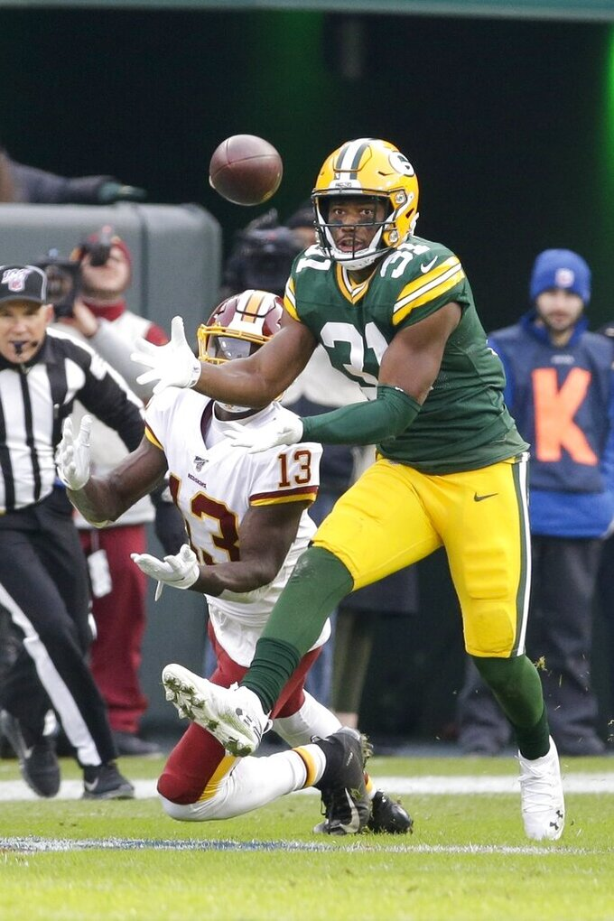 Green Bay Packers' Adrian Amos intercepts a pass in front of Washington Redskins' Kelvin Harmon during the first half of an NFL football game Sunday, Dec. 8, 2019, in Green Bay, Wis. (AP Photo/Mike Roemer)