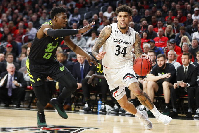 Cincinnati's Jarron Cumberland (34) drives past South Florida's Justin Brown (13) in the first half of an NCAA college basketball game, Tuesday, Jan. 15, 2019, in Cincinnati. (AP Photo/John Minchillo)