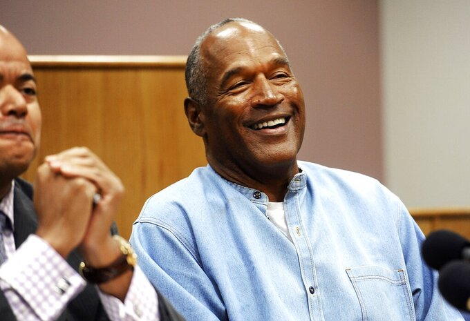 FILE - In this July 20, 2017, file photo, former NFL football star O.J. Simpson reacts after learning he was granted parole at Lovelock Correctional Center in Lovelock, Nev. Simpson got into a series of minor legal scrapes following his 1995 acquittal of murder charges in the deaths of his wife Nicole Brown Simpson and her friend Ronald Goldman. (Jason Bean/The Reno Gazette-Journal via AP, Pool, File)