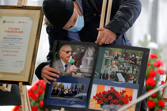 A man adjusts images of Iancu Tucarman, during his funeral, at a Jewish cemetery in Bucharest, Romania, Monday, Jan. 11, 2021. Tucarman, one of the last remaining Holocaust survivors in Romania, on was buried after dying from COVID-19 last week at the age of 98. (AP Photo/Vadim Ghirda)