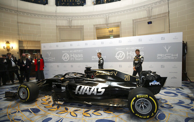 Drivers Romain Grosjean, right, and Kevin Magnussen pose during the unveiling of their new Rich Energy Haas F1 Team 2019 car, launched at the Royal Automobile Club in London, Thursday Feb. 7, 2019. (Steven Paston/PA via AP)