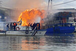 In this photo provided by the Philippine Coast Guard, members of the Philippine Coast Guard try to extinguish flames on a burning cargo ship docked in Manila, Philippines, Saturday, June 12, 2021. The fire and a powerful blast ripped through ship docked to refuel in the Philippine capital of Manila on Saturday, injuring at least six people and igniting a blaze in a nearby riverside slum that gutted dozens of shanties, officials said. (Philippine Coast Guard via AP)