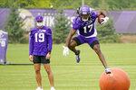 Minnesota Vikings wide receiver K.J. Osborn (17) runs a pass play, leaping over a large ball, as wide receiver Adam Thielen watches during the NFL football team's training camp, Thursday, Aug. 5, 2021, in Eagan, Minn. (AP Photo/Jim Mone)