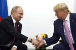FILE - In this June 28, 2019, file photo, President Donald Trump, right, shakes hands with Russian President Vladimir Putin, left, during a bilateral meeting on the sidelines of the G-20 summit in Osaka, Japan.  (AP Photo/Susan Walsh, File)
