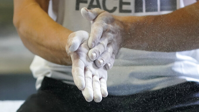 """Nathaniel Coleman rubs his hands before climbing during practice on Wednesday, May 26, 2021, in Salt Lake City. """"For the most part, people were psyched,"""" American Olympic climber Coleman said. """"They knew the sport would get more attention, a lot more inflow of money and kind of be recognized as the high-quality sport that it is."""" Climbing is an Olympic sport for the first time, and the spotlight will introduce a massive audience to what can be a lonely pursuit. (AP Photo/Rick Bowmer)"""