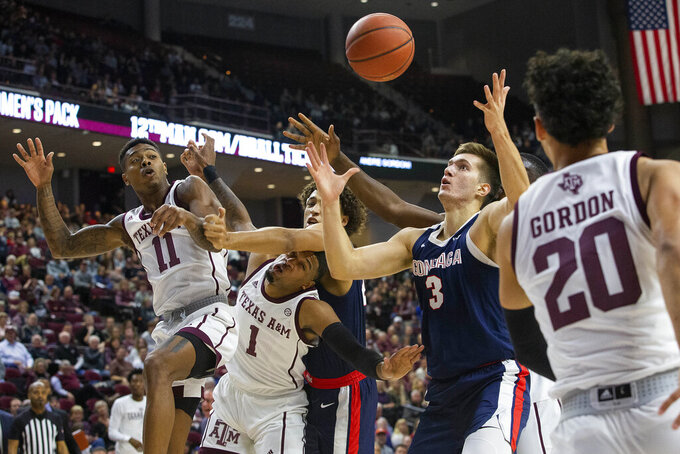 Gonzaga forward Filip Petrusev (3) and forward Anton Watson compete for a rebound against Texas A&M guards Wendell Mitchell (11) and Savion Flagg (1) during the first half of an NCAA college basketball game Friday, Nov. 15, 2019, in College Station, Texas. (AP Photo/Sam Craft)