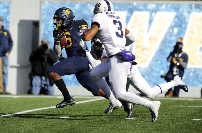 West Virginia running back Kennedy McKoy (6) runs for a touchdown while being chased by TCU cornerback Jeff Gladney (12) and safety Markell Simmons (3) during the first half of an NCAA college football game Saturday, Nov. 10, 2018, in Morgantown, W.Va. (AP Photo/Raymond Thompson)