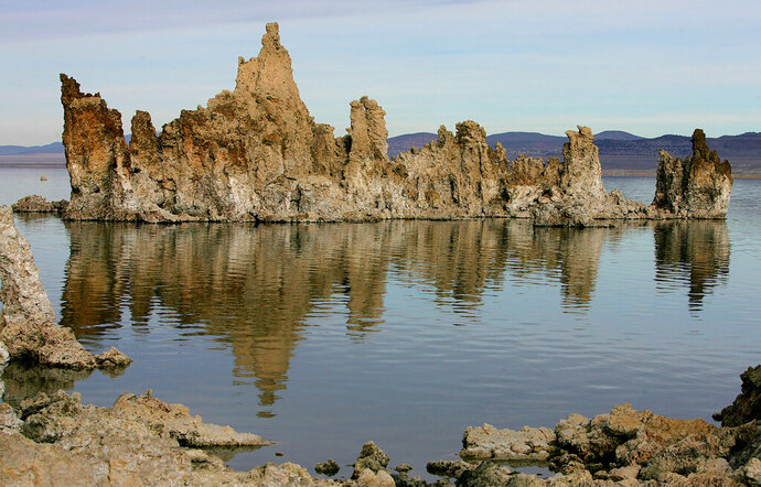 FILE - This Nov. 15, 2004 file photo shows tufa towers in Mono Lake near Lee Vining, Calif. Federal firefighters have set fire to invasive non-native weeds on an island in the Sierra Nevada's Mono Lake in an effort to clear space for California gulls to build their nests on the ground. The burn Friday, Feb. 14, 2020 cleared nearly half of 11-acre (4.45-hectare) Twain Island, the Los Angeles Times reported. The lake is an important nesting ground for gulls but the recent arrival of an Eurasian bush known as five-horn smotherweed has left little room for nesting. (AP Photo/Ben Margot, File)