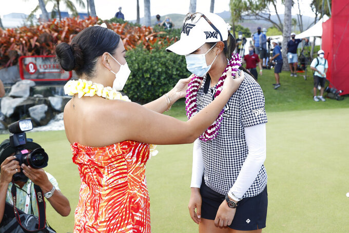 A hula dancer places a flower lei on Lydia Ko, of New Zealand, right, after Ko won the Lotte Championship golf tournament, Saturday, April 17, 2021, in Kapolei, Hawaii. (AP Photo/Marco Garcia)