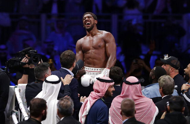 Britain's Anthony Joshua celebrates after beating Andy Ruiz Jr. to win their World Heavyweight Championship contest at the Diriyah Arena, Riyadh, Saudi Arabia. (AP Photo/Hassan Ammar)